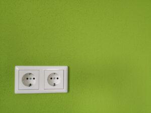 Weiße Steckdose an grüner Wand